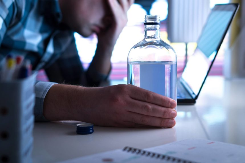 Man leaning on desk with alcohol and laptop