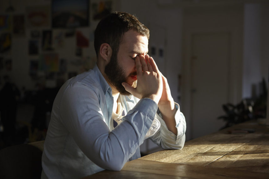 depressed, anxious man sitting at table holding his head