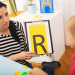 child psychiatris holding the letter 'R' in front of a child
