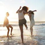 girls on beach kicking water
