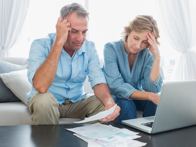 worried couple paying bills on laptop