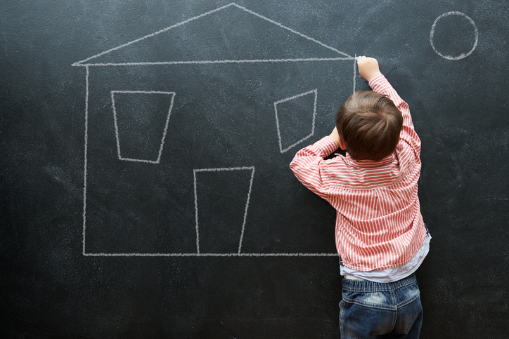 child drawing house on chalkboard