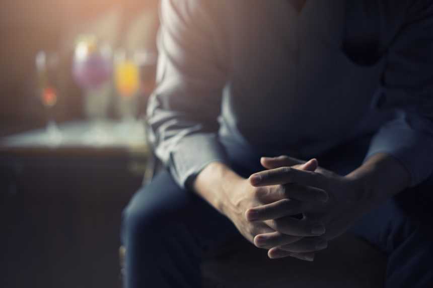 depressed businessman leaning forward with hands together with drinks behind him