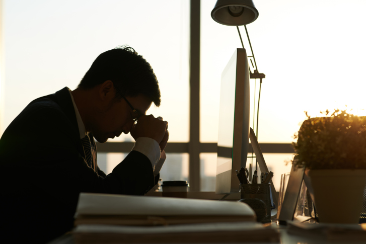 office worker rests head on clasped hands in exhaustion
