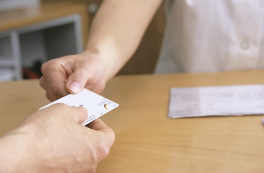 person handing health insurance card