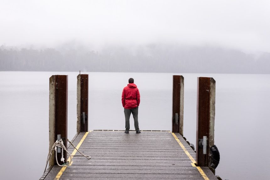 man looking out at a lake