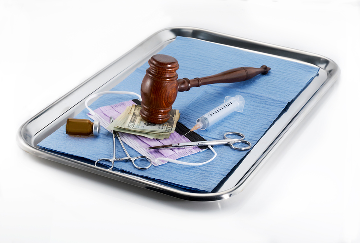 gavel on doctor's tray with money