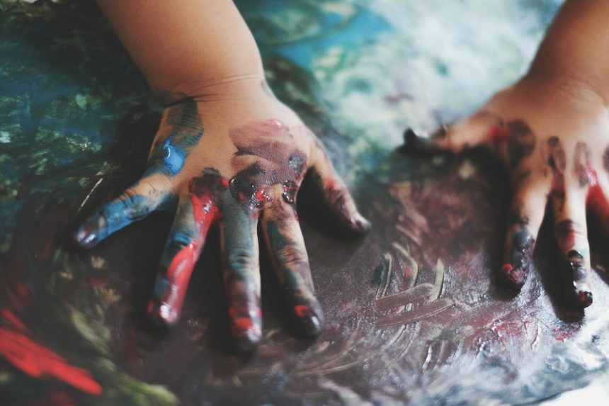 child painting with their hands