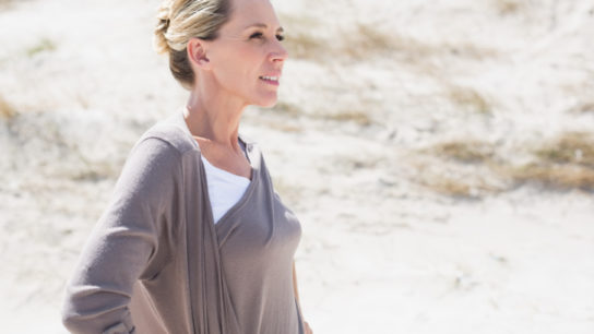 woman on beach looks peacefully and thoughtfully forward