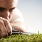 man trimming grass blade to be even with the others