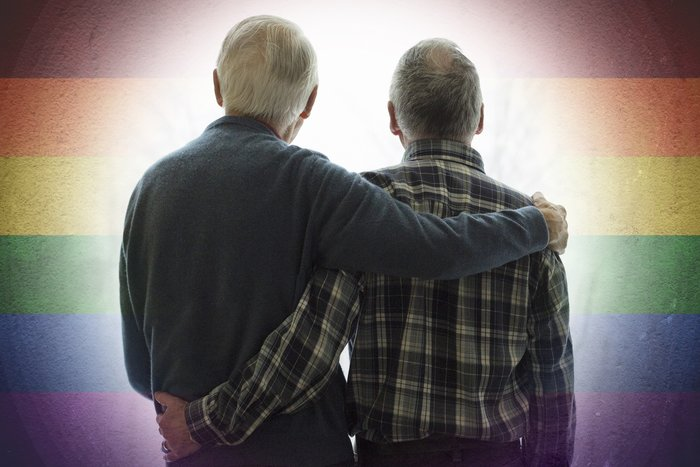 elderly gay couple in front of LGBTQ rainbow colors