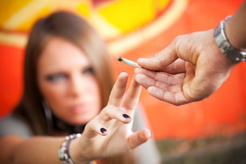 young girl reaching for a joint to smoke