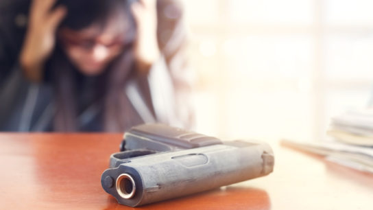 devastated man with hands on head sits in front of gun on table