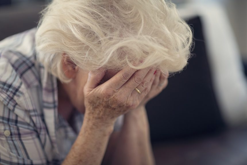 older woman with hands over face, upset