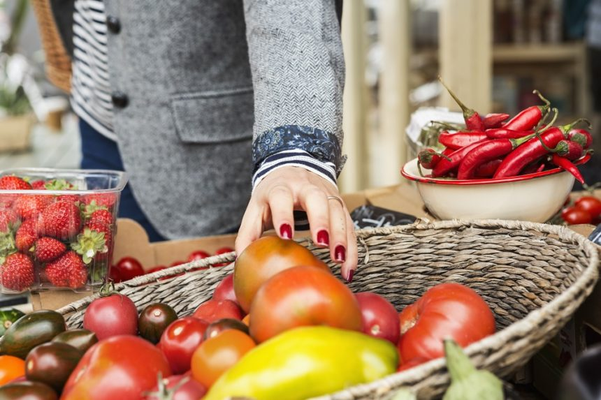 woman reaching for a tomato