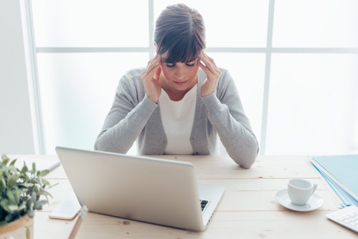 businesswoman in front of laptop holds her head in her hands