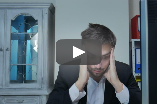 Stressed man in suit holding head in his hands