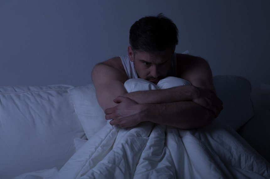 man in bed with anxiety