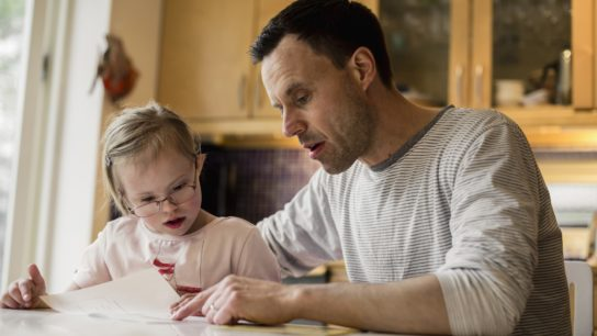 child with Down syndrome sitting with father