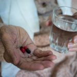 elderly woman holding pills in hand