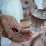 elderly woman holding pills in hand