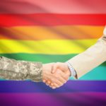 soldiers shaking hands in front of gay flag