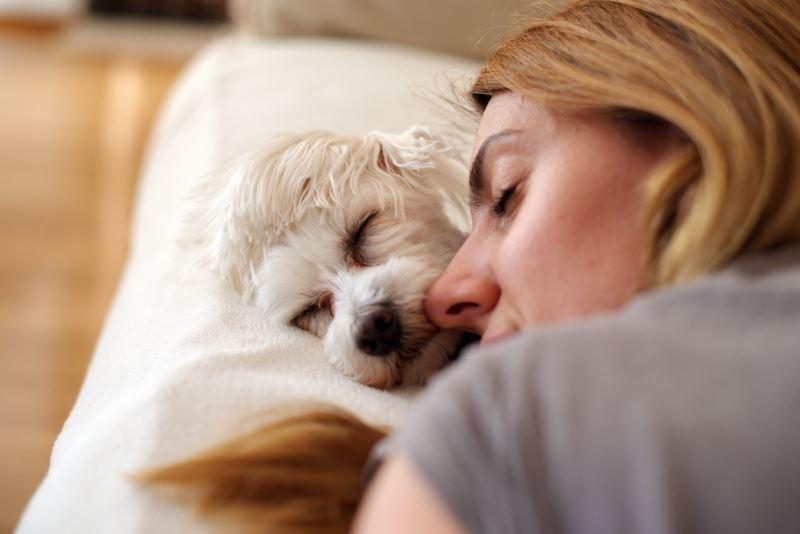 A woman cuddling her dog