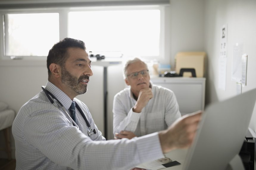 doctor showing computer to patient
