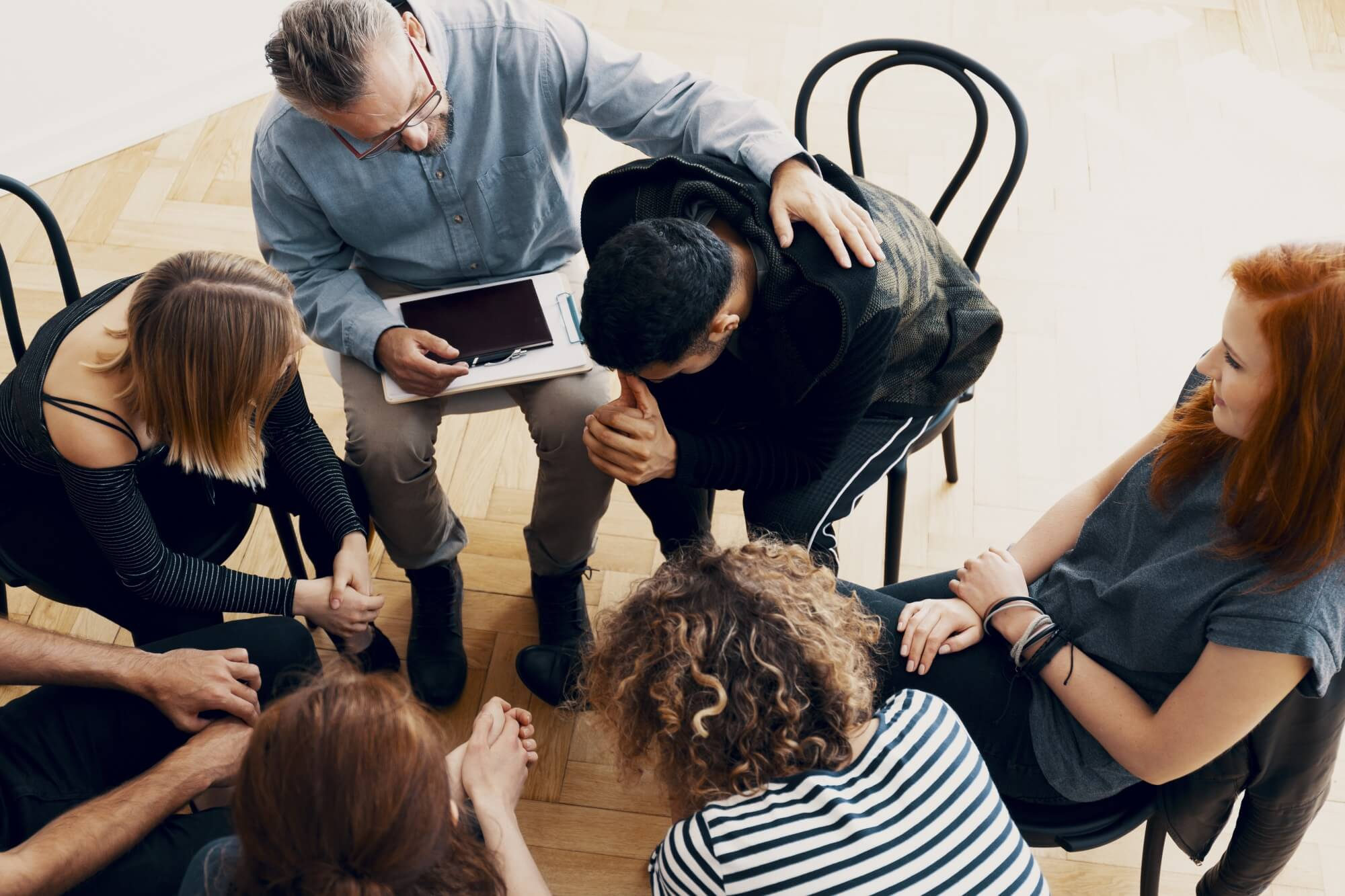 Group of adults and therapist sitting in a circle.