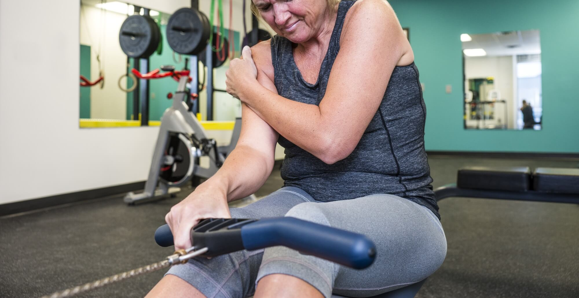 Exercising woman holding shoulder in pain