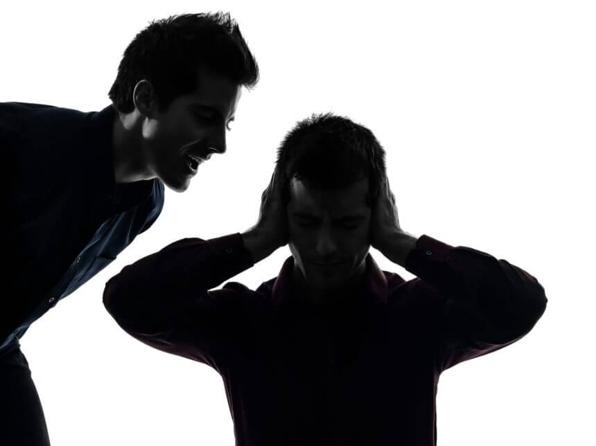 man yelling at man holding his hands over his ears