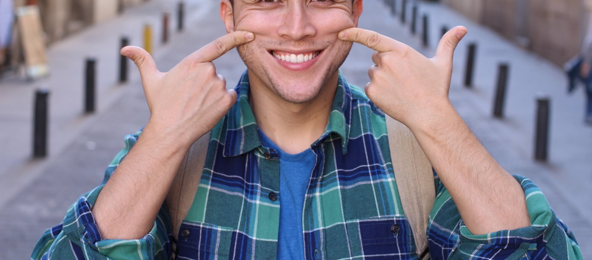 Man holding up the corners of his mouth in a smile