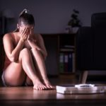 Young woman crying in front of a scale