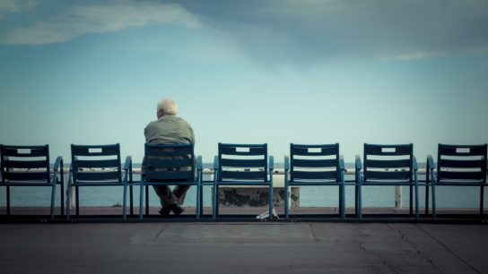 Older man sitting in chair on balcony