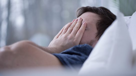 Man in bed with hands over his face