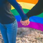 Two people holding hands in front of LGBTQ flag