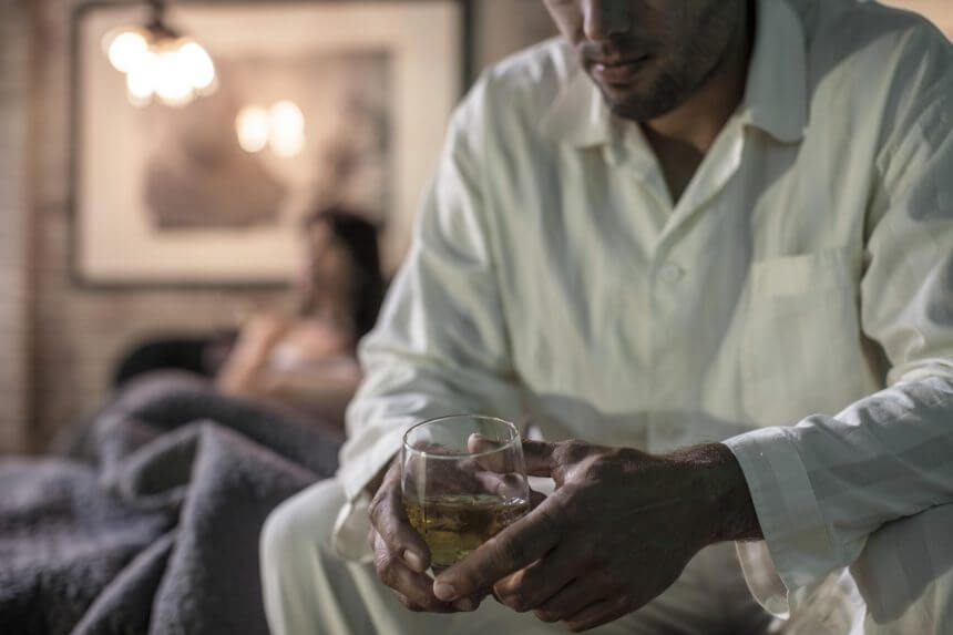 Man sitting on bed with a glass of alcohol