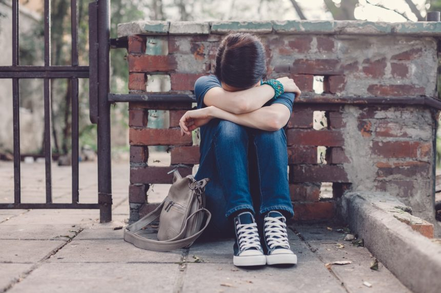 young girl, adolescent, head down, depression, mental health
