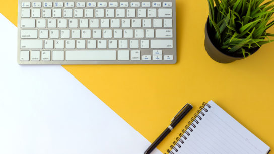 Keyboard with pen, paper and plant on a desk