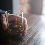 man holding glass of brown liquor, alcohol