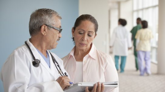 Male doctor explaining results to middlea-ged female patient in hallway